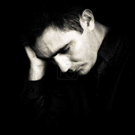 Photo for Black and white portrait of a worried and depressed man isolated on black - Royalty Free Image