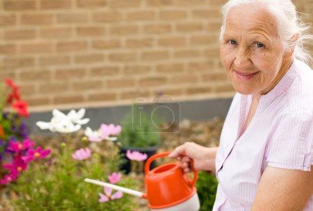 Photo pour Portrait estival de femme âgée arrosant ses fleurs - image libre de droit