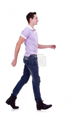Photo for Side view of a fashion man walking forward over white . young casual man walking from left to the right of the camera - Royalty Free Image