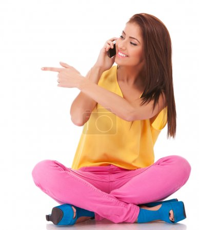 Seated casual woman talking on phone and pointing