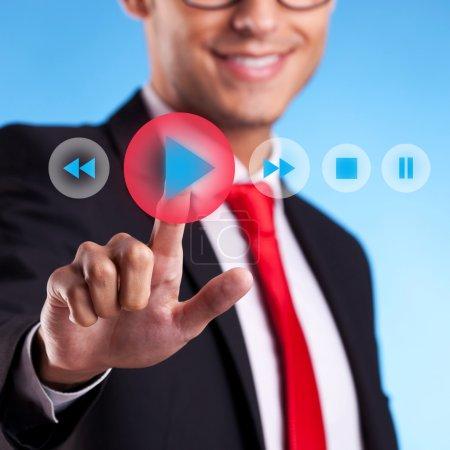 Photo pour Jeune homme d'affaires appuyant sur un bouton de lecture sur un écran virtuel - image libre de droit