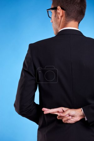 Business man with fingers crossed behind back