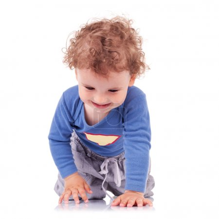 Curly-haired little boy crawling happily