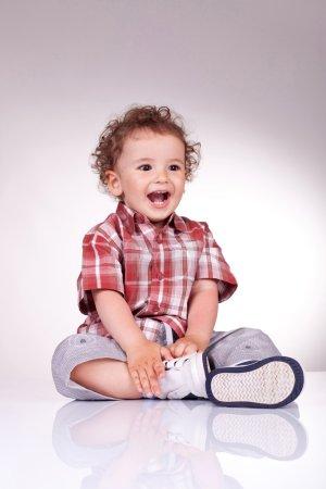 Photo pour Joyeux petit garçon qui rit. Il est assis et tient sa jambe. Sur fond gris . - image libre de droit