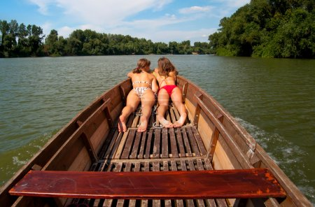 Cute teenage girls sunbathing in the boat on sunny summer day