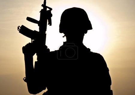 Photo for Silhouette of young soldier against the sun - Royalty Free Image