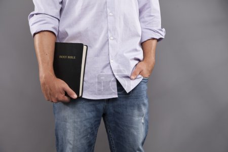Man Casually Holds Bible