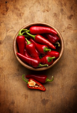 Photo for Red Hot Chili Peppers in bowl over wooden background - Royalty Free Image