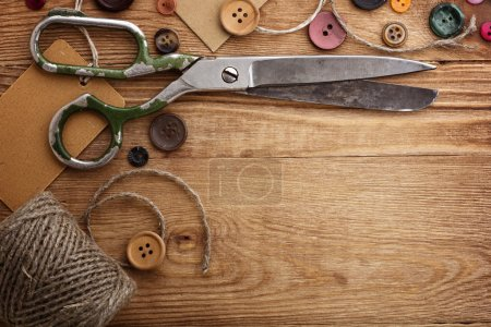 Photo for Old scissors and buttons on the wooden table - Royalty Free Image