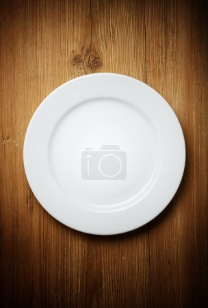 Photo for Empty white plate on wooden table - Royalty Free Image