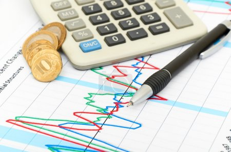Calculator, coins and pen laying on chart. Concept of finance.