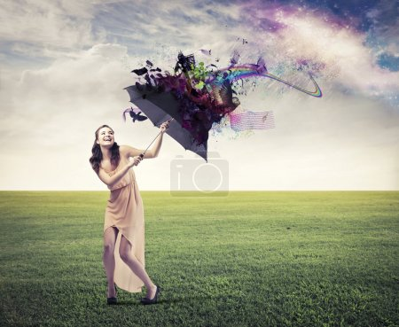 Photo for Laughing beautiful woman on a green meadow sheltering from the rainbow under an umbrella - Royalty Free Image