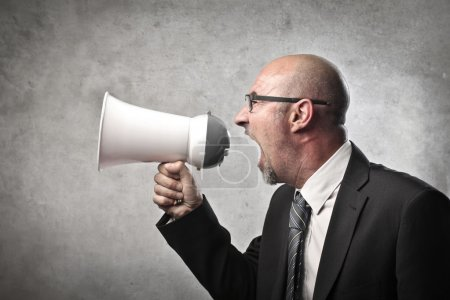 Photo for A businessman is screaming into a megaphone. - Royalty Free Image