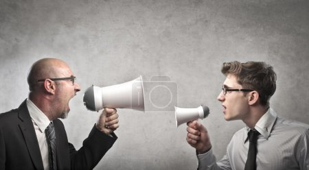 Photo for A leader is shouting, into a megaphone, against an employee. - Royalty Free Image