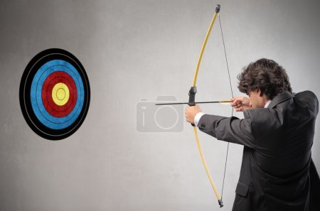 Photo for A businessman is hitting a target very close to him. - Royalty Free Image