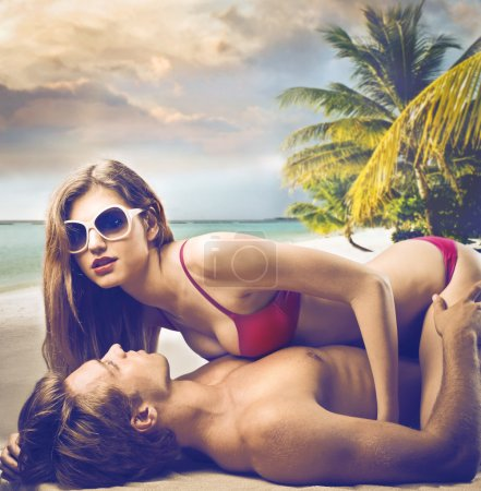 Photo for Two young lovers are making sex on a beautiful beach. - Royalty Free Image