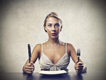 Photo pour Une blonde mignonne fille est prête à manger. - image libre de droit