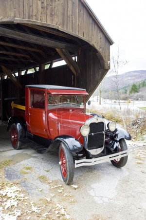 Old car at covered wooden bridge, Vermont, USA