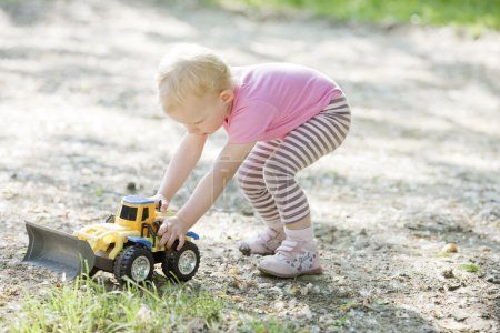 Little girl playing with little excavator