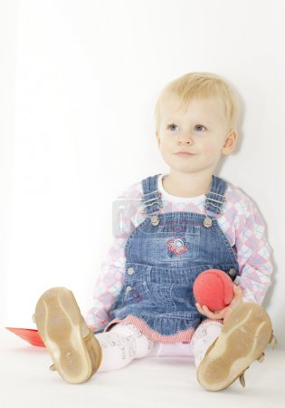 Sitting toddler with a ball