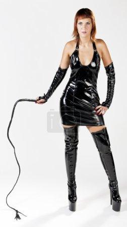 Photo pour Femme portant des vêtements extravagants tenant un fouet - image libre de droit