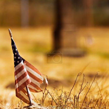 Photo pour Usée du drapeau américain contre un séchées sur fond de champ. - image libre de droit