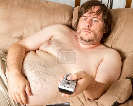 Photo for Fat man is laying on the couch topless watching the TV. Guy is overweight and quite lazy looking. - Royalty Free Image