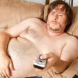 Fat man is laying on the couch topless watching th...