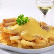 Cheese topped fish fillets served with French frie...