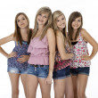 Four teenage girls in summer clothes standing, iso...