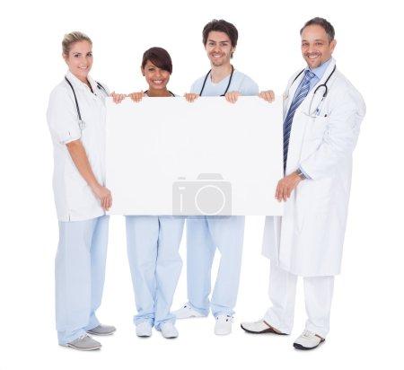 Foto de Grupo de médicos presentando tablero vacío. Aislado sobre blanco - Imagen libre de derechos
