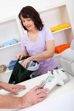 Photo pour Assistant vente et emballage t-shirts en magasin - image libre de droit