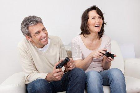 Mature couple enjoying videogames