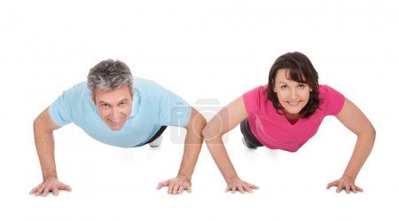 Active mature couple doing pushups