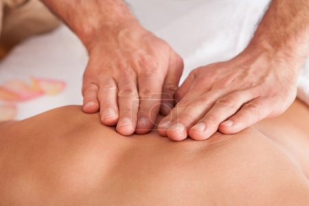 Photo for Beautiful young woman getting back massage at spa - Royalty Free Image