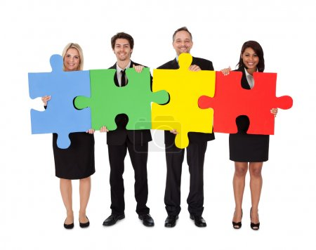 Group of business assembling puzzle