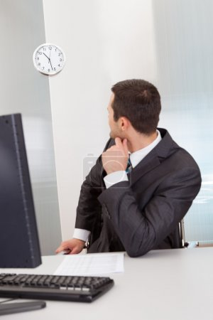 Businessman looking at clock at the office