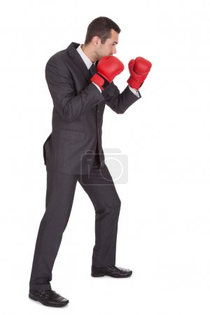 Competitive businessman in boxing gloves