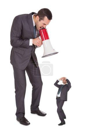 Boss screaming in megaphone at employee