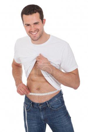 Muscular man measuring waist