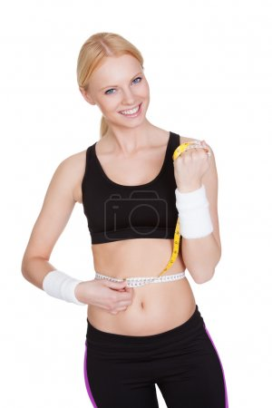Beautiful fitness woman measuring waist
