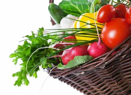Photo pour Composition avec légumes crus, feuilles vertes et panier en osier isolé sur fond blanc. Espace de copie - image libre de droit