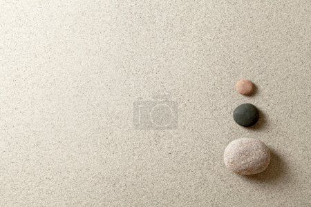 Photo for Three colorful zen stones at right side of sand background - Royalty Free Image