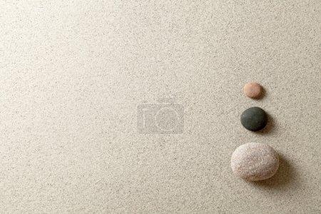 Photo pour Trois pierres zen colorées sur le côté droit du fond de sable - image libre de droit