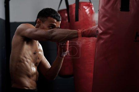 Photo pour Action d'un chasseur d'arts martiaux Boxe formation sur un sac de boxe dans la salle de gym - image libre de droit