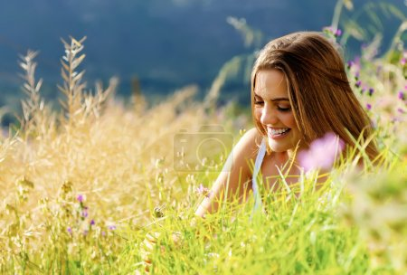 Photo for Carefree woman sitting in a green field enjoying the summer sunlight - Royalty Free Image