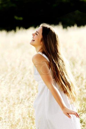 Photo pour Magnifique fille marchant dans le domaine de l'herbe longue et traînant sa main toucher l'herbe sèche tout en riant et souriant, mode de vie sain insouciant - image libre de droit