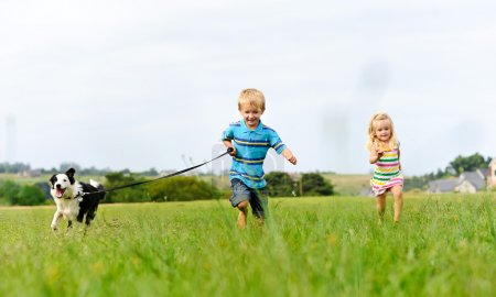 Photo for Young girl tries to catch up with her brother running ahead with their new puppy - Royalty Free Image