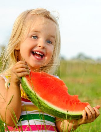 Cute blond girl happy with watermelon