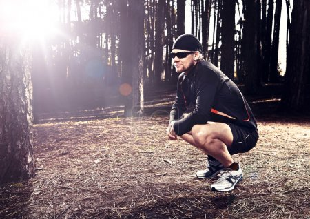 Photo for Athletic man resting after running in the forest - Royalty Free Image